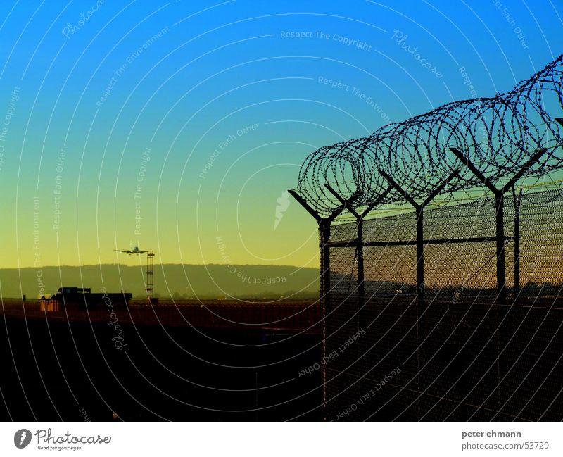 Dämmerflug blau Ferien & Urlaub & Reisen gelb Stimmung fliegen Luftverkehr Hügel Flughafen Zaun Flugzeuglandung Ankunft Stacheldraht halbdunkel aufsetzen