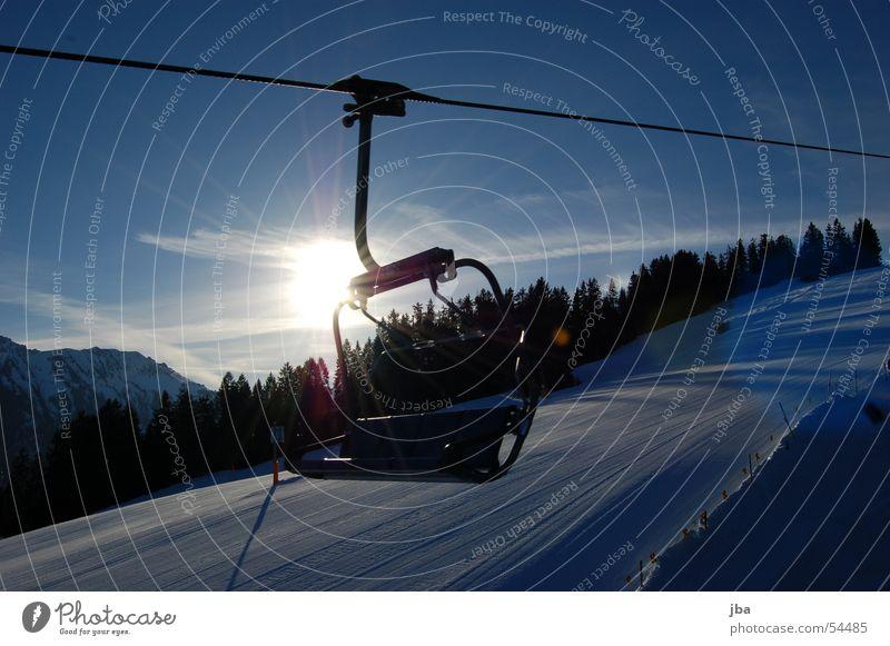 Sessel im Gegenlicht Sesselbahn fahren Haken Winter Sonnenaufgang Wald kalt Kunstschnee Gstaad Saanenland Sitzgelegenheit Seil sitzen Schnee Himmel