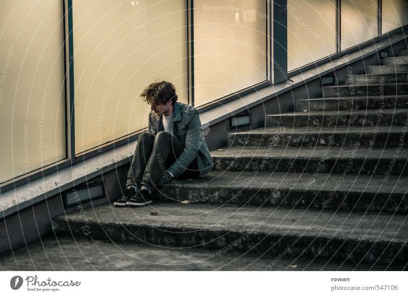 warten Mensch maskulin Junger Mann Jugendliche Erwachsene Stadt Fassade Fenster dunkel Treppe Glasfassade diagonal kalt sitzen Einsamkeit Sorge Traurigkeit