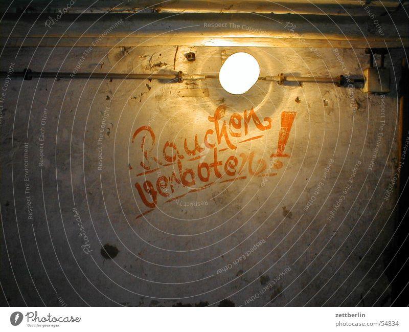 Rauchen verboten! Keller unterirdisch Bunker Glühbirne grell Verbote Nichtraucher dunkel braun Innenaufnahme verfallen Text Lateinische Schrift Hinweisschild