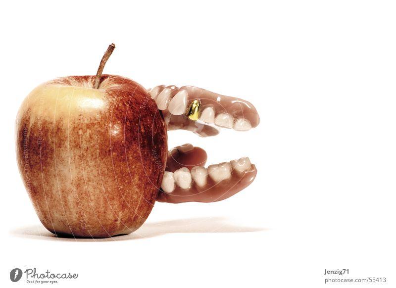 Fest zubeißen. Goldzahn Prothese Zahnersatz Haftcreme Apfel Frucht Ernährung Zähne