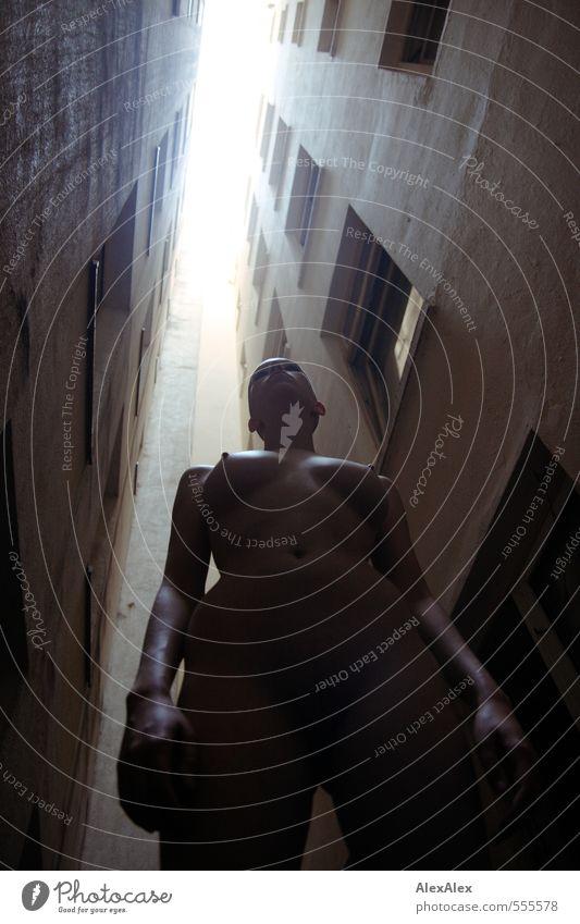 Nackte Frau steht in dystopisch wirkender Häuserschlucht Jugendliche Frauenbrust Bauch Bauchnabel Arme Kopf 18-30 Jahre Erwachsene Mehrfamilienhaus Lichthof
