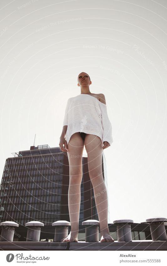 junge, große Frau mit sehr kurzen Haaren steht auf einem Schornstein vor einem Hochhaus Junge Frau Jugendliche 18-30 Jahre Erwachsene Dach Hochhausfassade