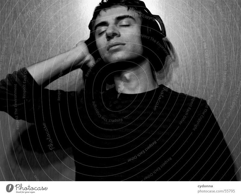 Menschenskind XI Mann Porträt Stil Wand Holz Hand Körperhaltung Pullover Musik hören Kopfhörer Licht Maserung Gesicht Gesichtsausdruck Schwarzweißfoto