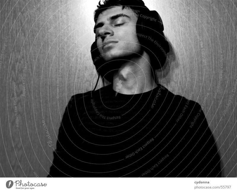Menschenskind XII Mann Porträt Stil Wand Holz Hand Körperhaltung Pullover Musik hören Kopfhörer Licht Maserung Gesicht Gesichtsausdruck Schwarzweißfoto