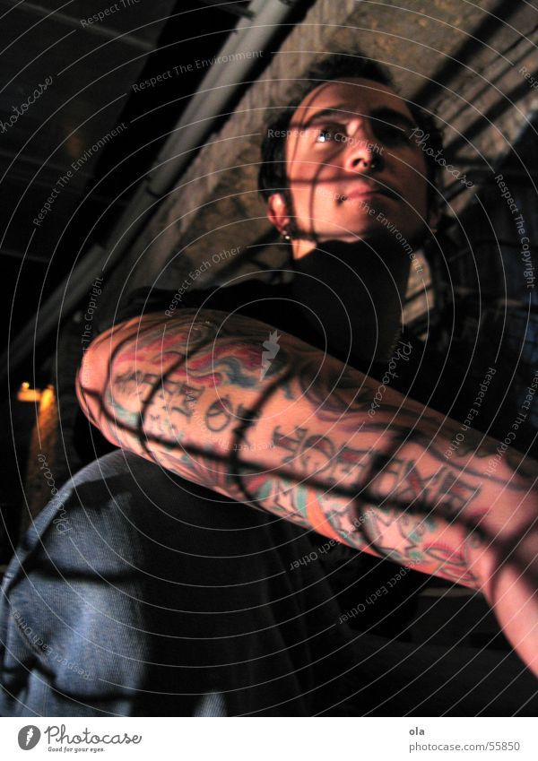 hinter gittern Mann Arme sitzen Treppe Backstein Tattoo Piercing Gitter Bielefeld