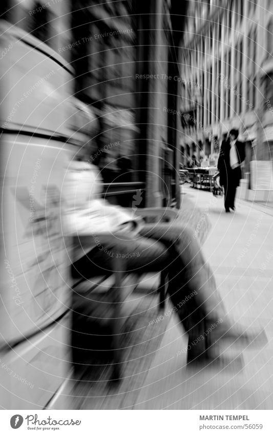 In der Ruhe liegt die Kraft. Schwarzweißfoto Außenaufnahme Unschärfe Bewegungsunschärfe Frau Erwachsene Beine Stadt Straße Jacke sitzen street Bürgersteig