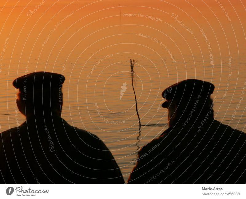 Männer im Sonnenuntergang Mann Wasser Sonne Meer ruhig See Abenddämmerung