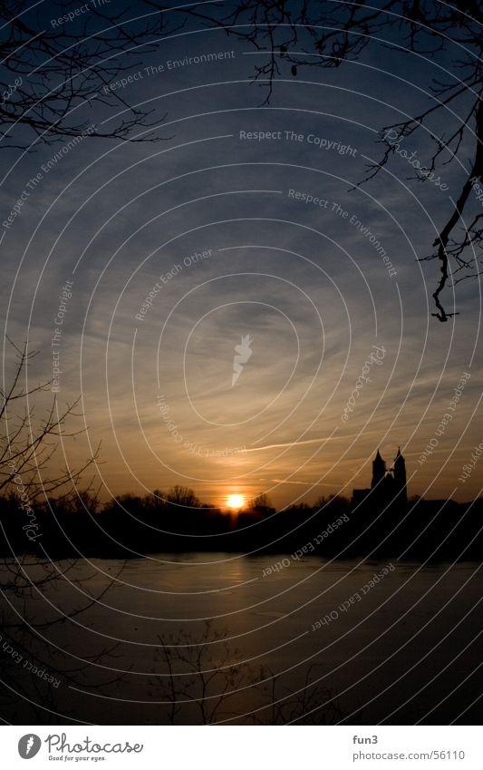 Sonnenuntergang in Magdeburg Himmel blau Winter Wolken See Eis Dom Hochformat