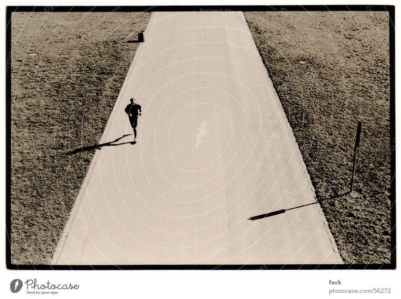Einsamer Jogger Joggen Einsamkeit Stimmung Außenaufnahme laufen Läufer Ferne weiter weg tiefstehende sonne Schwarzweißfoto