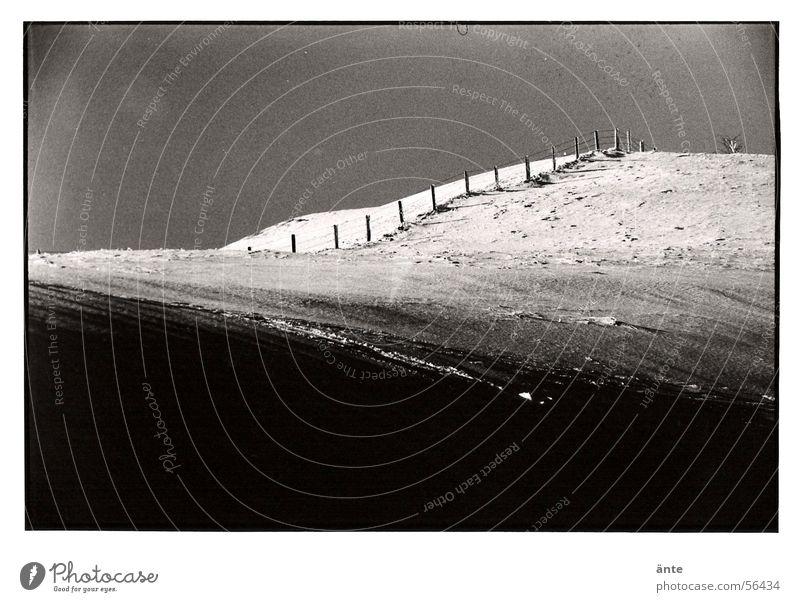 Zaun Winter kalt analog dunkel Hügel Vignettierung Fotolabor Schneelandschaft Ödland ruhig Einsamkeit Schwarzweißfoto Kontrast Landschaft Himmel Schatten