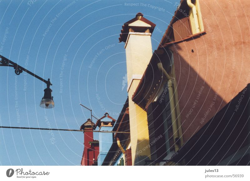 Italien Stadt Haus Lampe schwarz Dachgiebel Dachziegel mehrfarbig Licht Sommer hell Himmel blau Mauer Stein Schornstein Perspektive Farbe Ecke Schatten