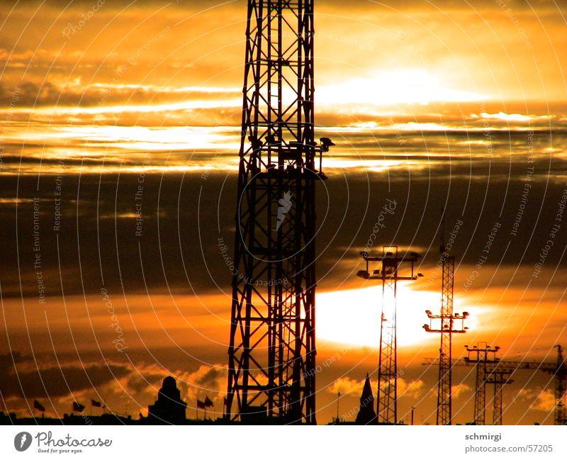 Sonne der Industrie Sonnenuntergang Hochspannungsleitung gelb schwarz Wolken Stimmung braun Himmel Abend orange Strommast ambience