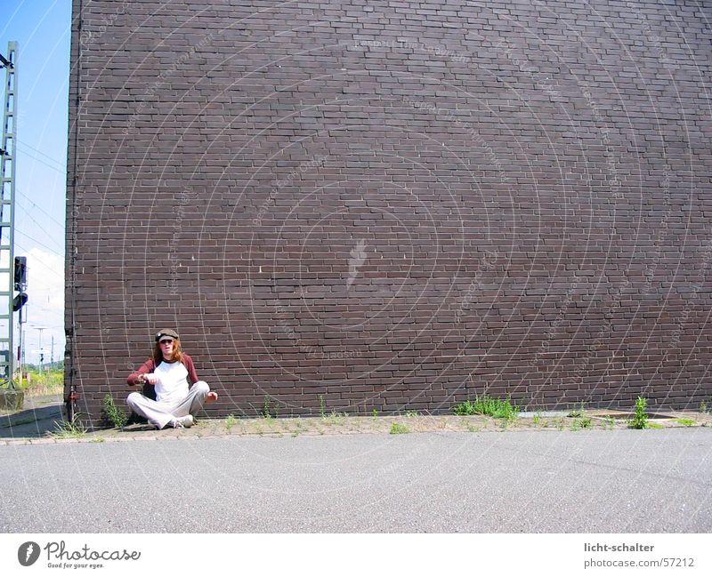 viele Steine - ein Mann Wand Mauer braun Asphalt Mütze Bahnhof