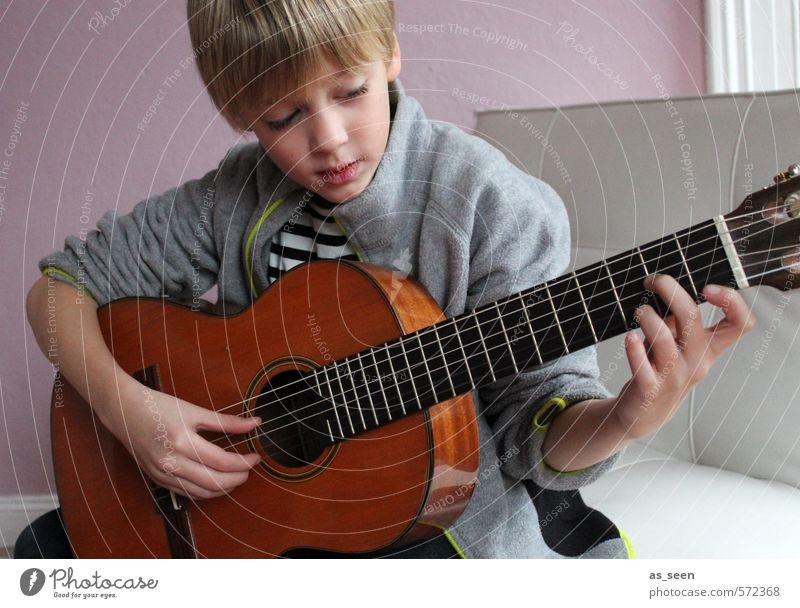 Der Junge mit der Gitarre maskulin 1 Mensch 3-8 Jahre Kind Kindheit Musik Musiker blond Holz berühren hören machen authentisch braun grau rosa weiß Stimmung