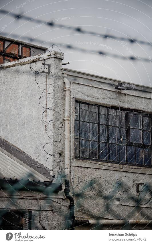 Knast Haus Industrieanlage Fabrik Bauwerk Gebäude Architektur Mauer Wand Fassade Fenster Aggression dunkel gruselig stachelig Stacheldraht Stacheldrahtzaun