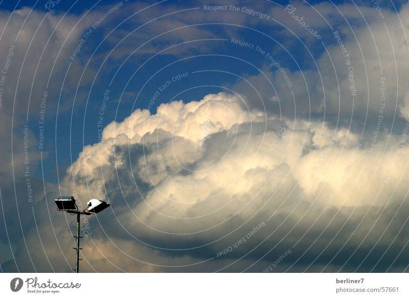 Frühlingswolken über dem Sportplatz Wolken Lampe Flutlicht Kunstlicht weiß grau Himmel wolkenstruktur Scheinwerfer blau