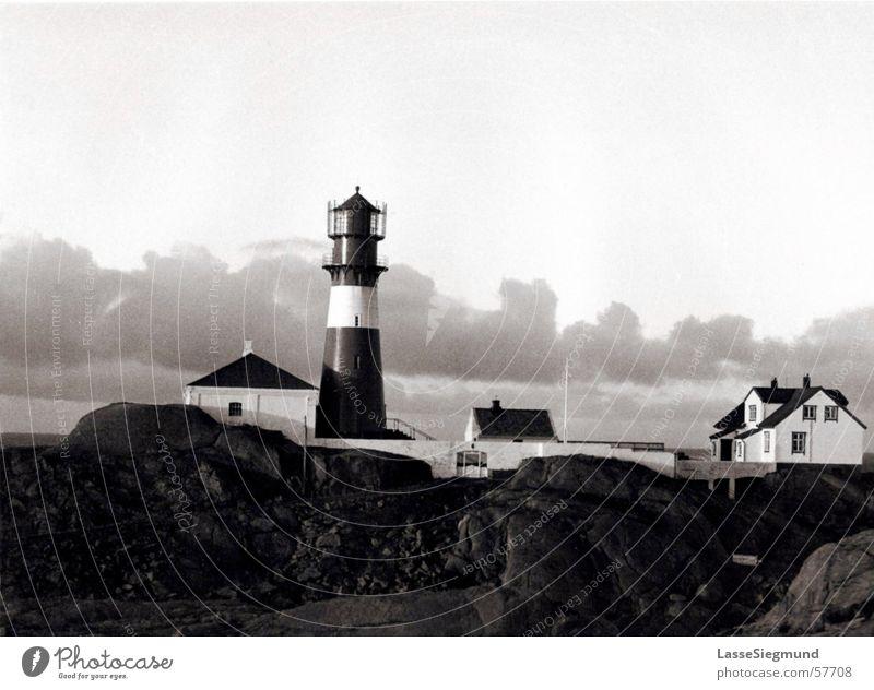 Leuchtturm Himmel weiß Strand Haus schwarz Wolken Einsamkeit Küste Felsen Insel Idylle historisch Norwegen Holzhaus Leuchtturmwärter