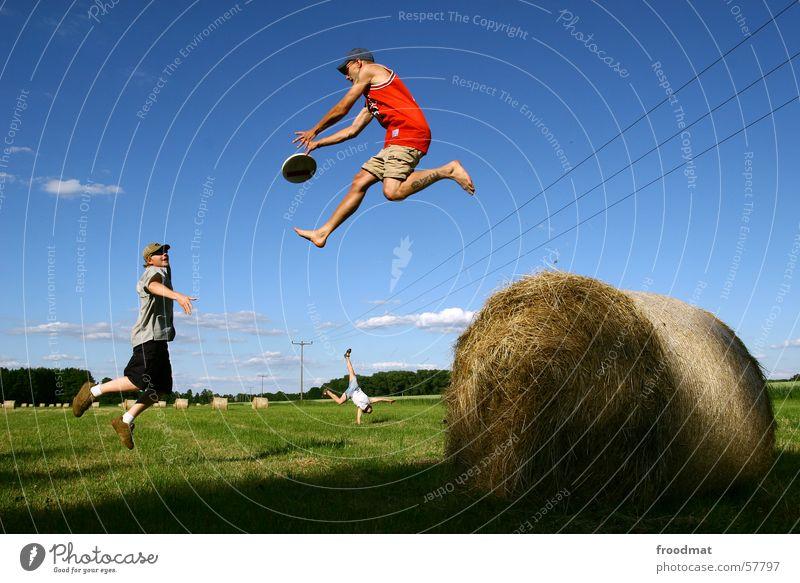 dynamisches Frisbeespiel springen Feld Wiese Handstand Heurolle Strommast fangen Heuballen Elektrizität hüpfen gleichzeitig Sport Spielen Aktion Ausgelassenheit