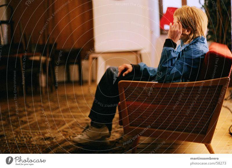 Nachdenken im Sofa gemütlich Teppich rot Junge Frau Hose Turnschuh blond Denken besonnen Innenaufnahme nicht hell nicht dunkel alt holzlehne blaue jacke sitzen