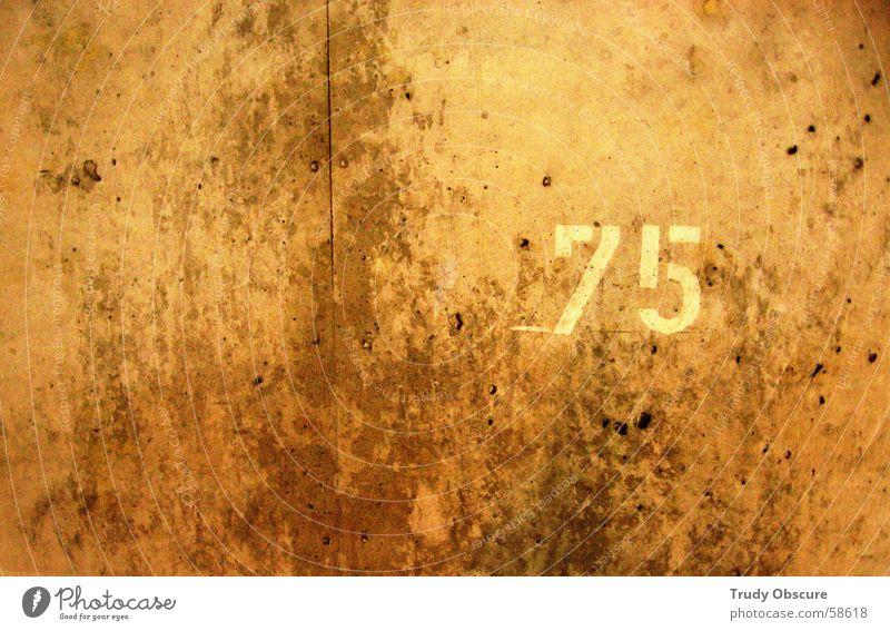 postcard no. 75 Wand Mauer Barriere Wegrand Ziffern & Zahlen braun gelb dunkel rechts links verfallen Parkhaus parken Beton Betonklotz Grenze betrag orange hell