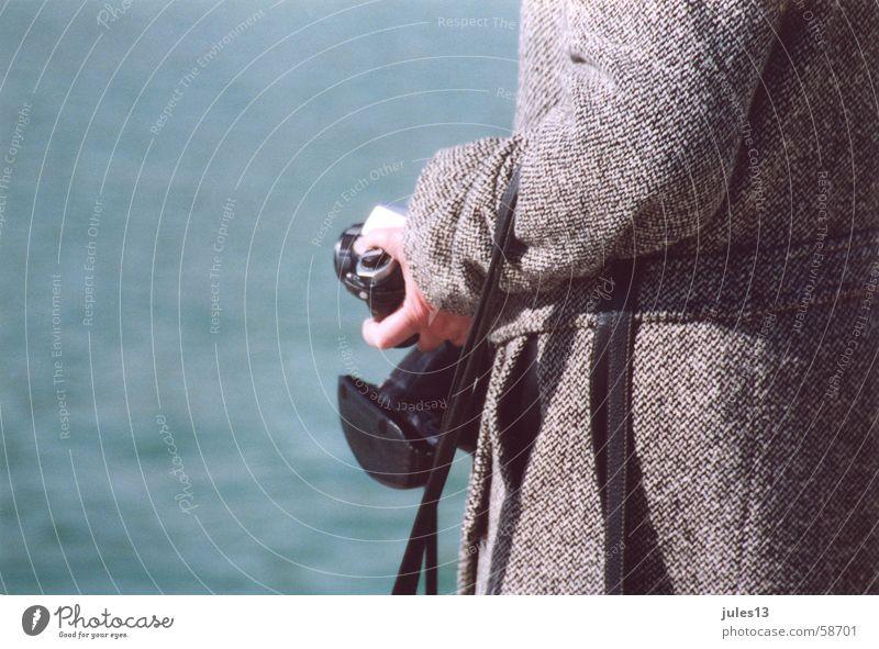 aus der hand Mantel grau Meer See Außenaufnahme Hand Dame blau Fotokamera Detailaufnahme am tag Licht Anschnitt