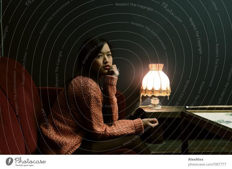 Gegenrede Lounge Junge Frau Jugendliche 18-30 Jahre Erwachsene Rock Pullover schwarzhaarig langhaarig Sofa Tischlampe Beistelltisch beobachten Kommunizieren