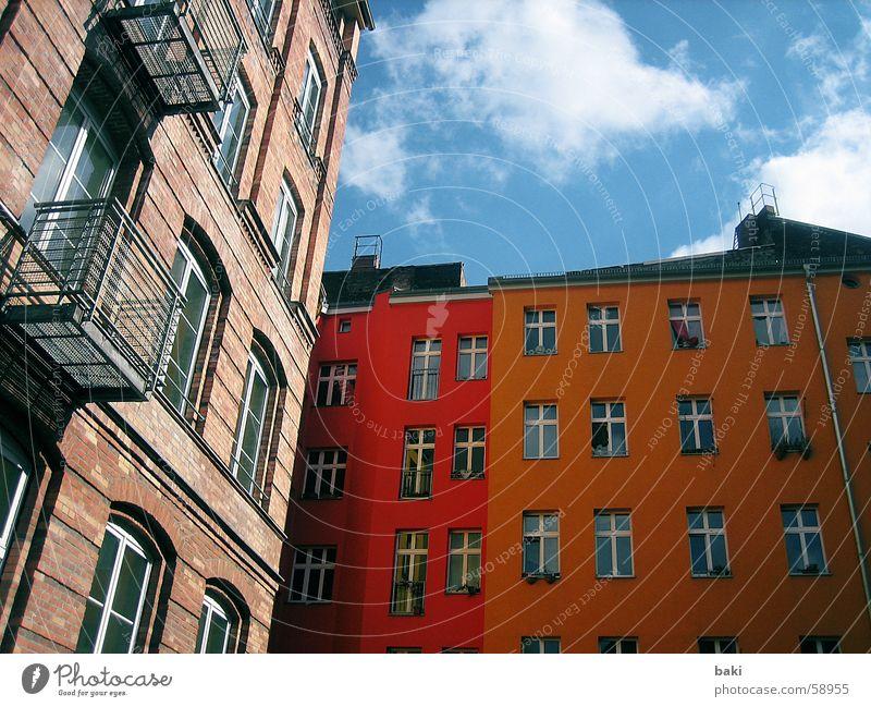 Hinterhof in Berlin Haus gelb Wolken orange blau Farbe Himmel Freude Freiheit außenaufname