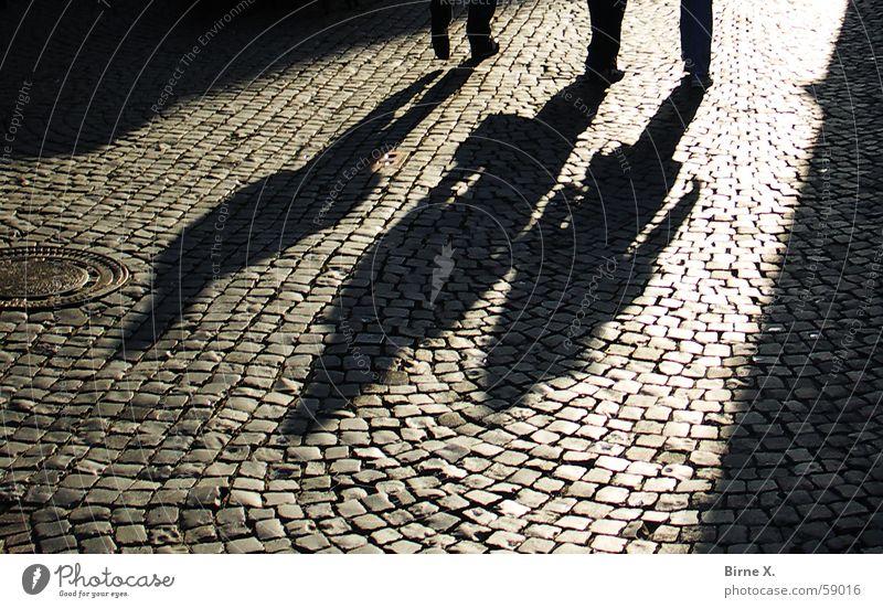 Shadows Mensch Sonne dunkel Fuß 3 Platz bedrohlich tief Kopfsteinpflaster Straßenbelag Pflastersteine unheimlich Gasse
