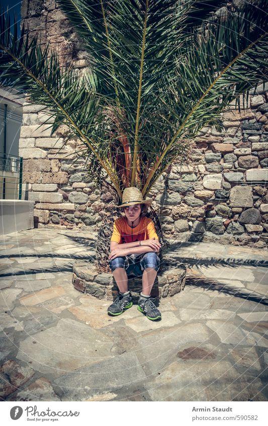 Müder Tourist / Junge sitzt unter einer Palme. Mensch Kind Natur Jugendliche Ferien & Urlaub & Reisen Sommer Erholung Wand Gefühle Mauer braun Freizeit & Hobby
