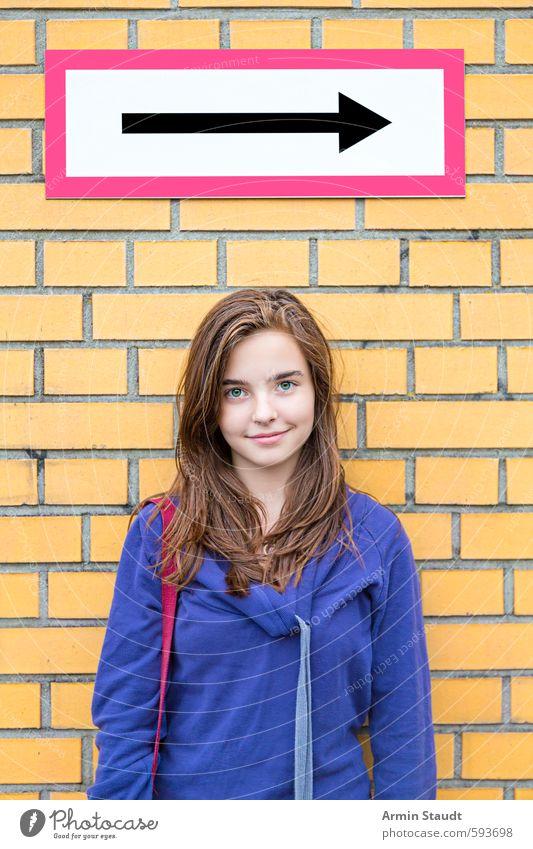 Lächelndes Mädchen vor einer Backsteinmauer/Richtungspfeil Mensch Frau Kind Jugendliche blau schön Freude gelb Erwachsene Wand Gefühle feminin Mauer Glück