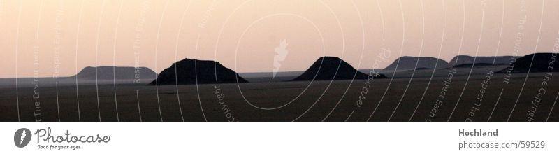 Weite Wüste Sonnenaufgang Morgen Hügel Kamel Luftspiegelung Steinwüste Ägypten Sudan Sehnsucht ruhig Fasten Unendlichkeit verloren Einsamkeit Ferne