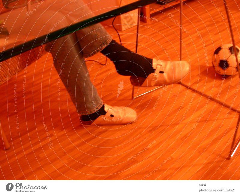 Fußball Hausschuhe bequem sitzen verschränken verschränkt Detailaufnahme Tischplatte Glastisch Gestell Holzfußboden Laminat Tischkante 1 Farbfoto Innenaufnahme