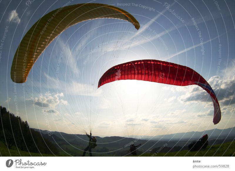 gleitschirmsession IV 2 rot gelb blenden Stimmung Wolken Gleitschirm Gleitschirmfliegen Fischauge grell Freude Extremsport Luftverkehr Paar Himmel Sonne
