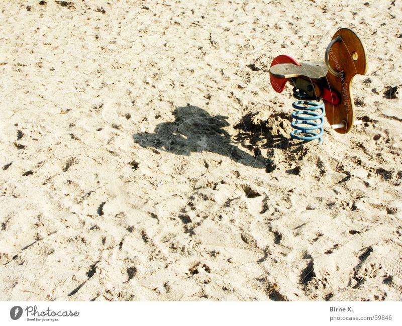 Vorsaison Spielplatz Strand Pferd Spielzeug Schaukel Wippe leer Einsamkeit Nebensaison Saison Spielen Holz Metallfeder Sand Schatten