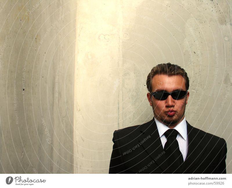 """""""Küsch misch"""" Mann Kerl Herr fein Anzug schwarz Sonnenbrille Küssen Lippen gespitzt Grimasse Bart Beton grau Wand lächerlich seltsam dumm Humor Typ Coolness"""