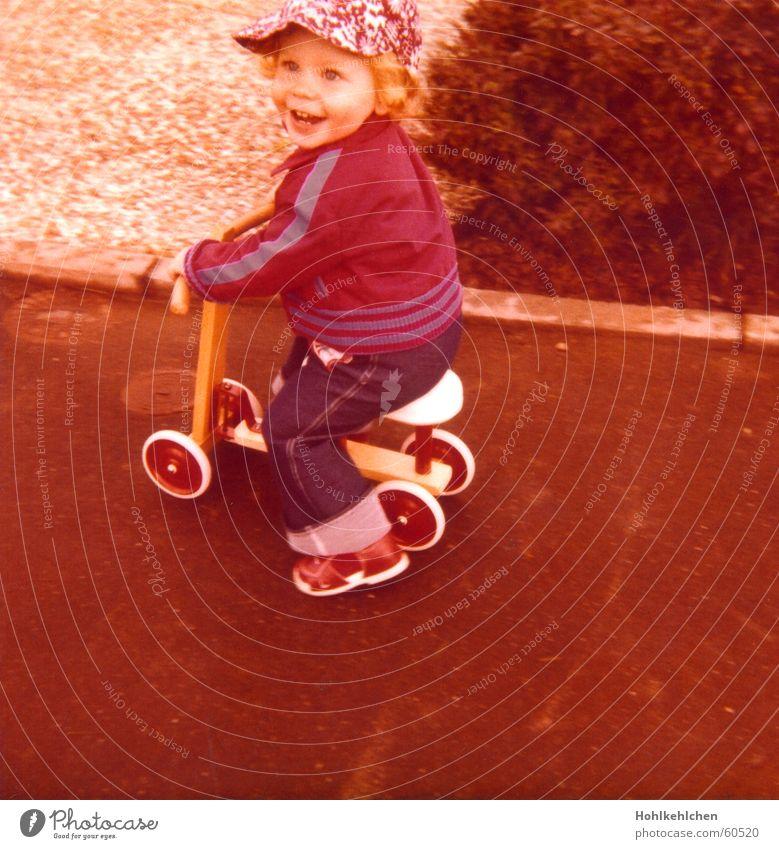 Neue Frühjahrskollektion Kind Freude Straße Junge lachen orange retro Jeanshose Spielzeug Jacke Hut Siebziger Jahre Stolz Tretroller Rocker 1979