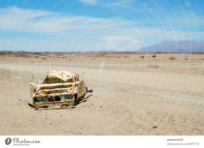 Karre im Sand Himmel blau ruhig Straße Stein PKW gefährlich trist bedrohlich Wüste trocken Afrika Rost Kiste Skipiste Namibia