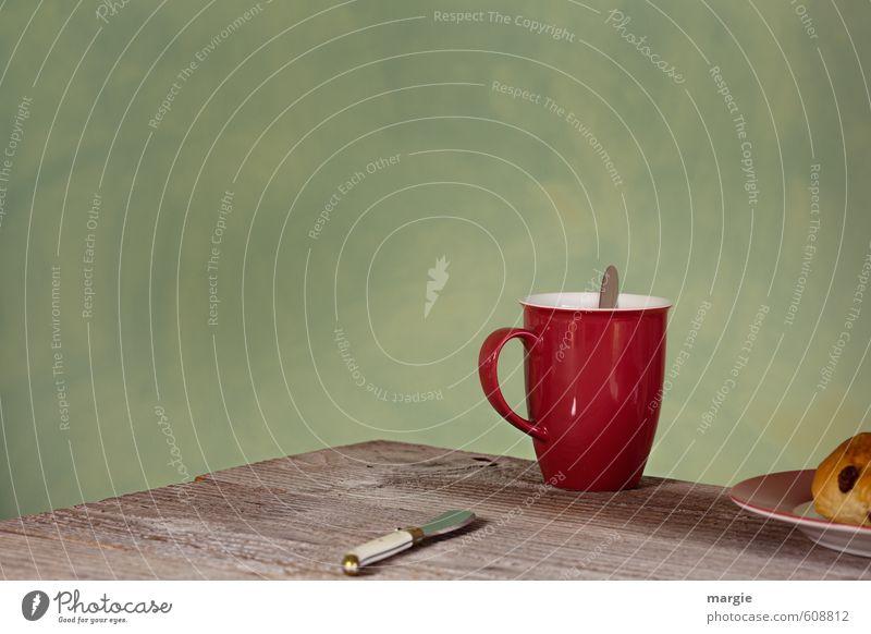 Eine rote Tasse, ein Messer und ein Brötchen auf einem Teller auf einem Holztisch vor einer grünen Wand Lebensmittel Rosinen Ernährung Frühstück Kaffeetrinken
