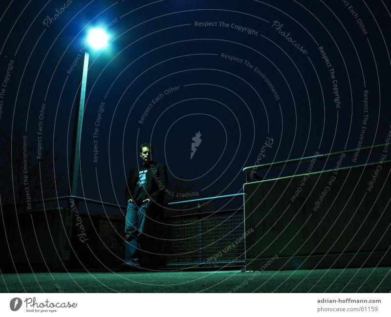 RIN UR Mann Kerl Hose Jacke Nacht dunkel Laterne Licht schwarz Beton Parkplatz Einsamkeit Trauer Gürtel Hand Tasche lässig Typ Jeanshose Pfosten Geländer