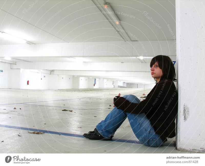 Allein in der Tiefgarage Frau blau Blatt Einsamkeit Ferne Wand Traurigkeit Linie hell warten sitzen Perspektive Trauer Zukunft Bodenbelag Flucht