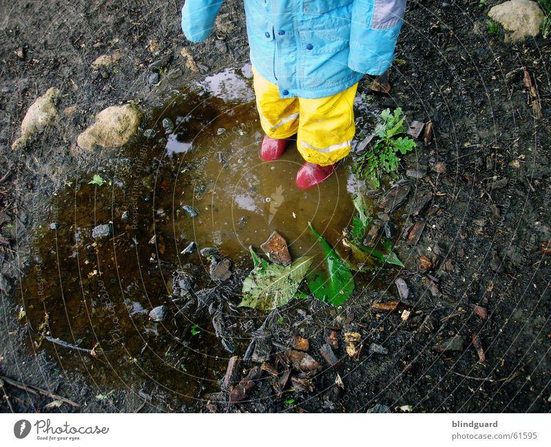 Matschepampe Kind Freude Regen dreckig nass Gewitter Pfütze Schlamm Gummistiefel schlechtes Wetter Regenjacke Regenbekleidung Regenhose