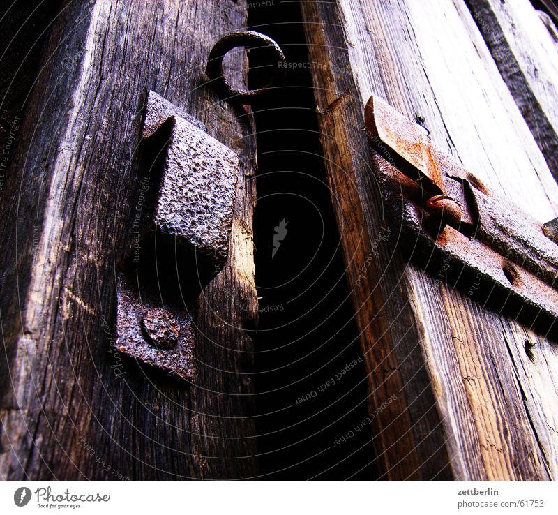 Spalt Riegel dunkel geschlossen geheimnisvoll gruselig Schlüssel Gartengeräte Harke Spaten Gießkanne Burg oder Schloss Scheune Rost Tür Spalte offen Schrecken