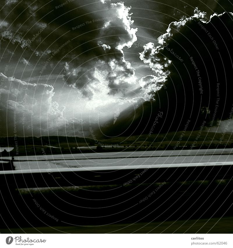 wolkig mit gelegentlichen Aufheiterungen Licht Sonnenstrahlen Wolken Wolkenberg bedrohlich dunkel Feld Rapsfeld Hügel Leitplanke Himmel Ferne Beleuchtung Lampe