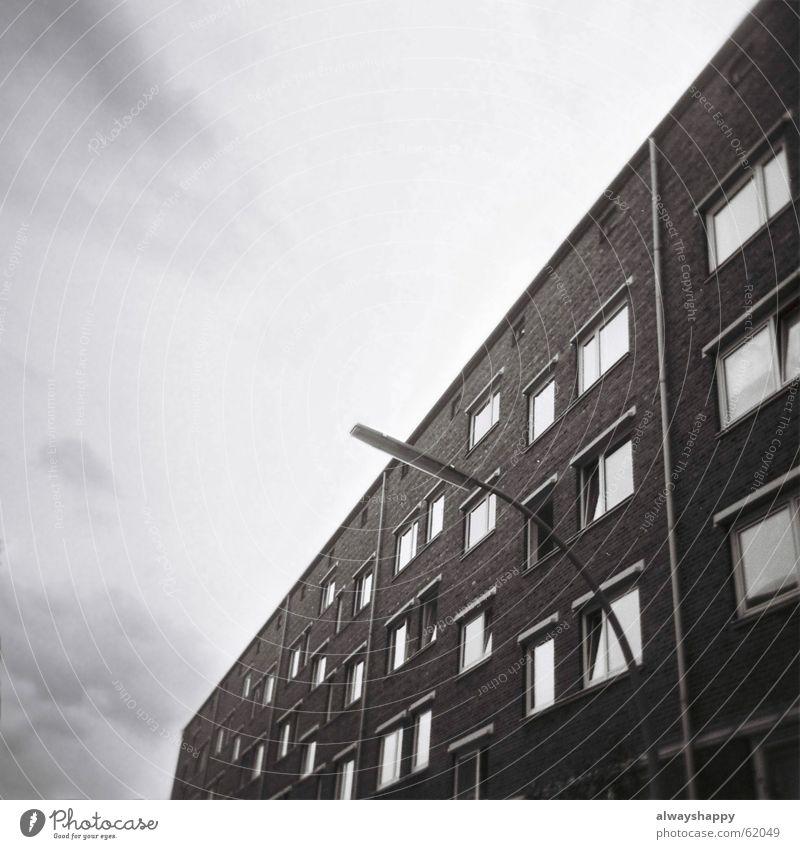 frühlingsgefühle Wolken Haus Herbst Fenster grau Lampe trist Backstein Laterne schlechtes Wetter Plattenbau Ghetto Wohnhochhaus Mittelformat karg