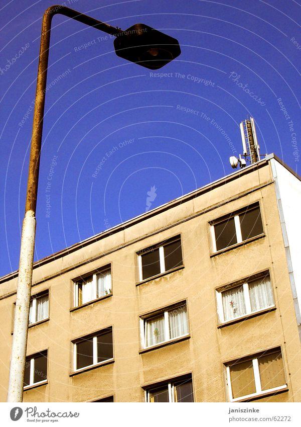 Zuhause. Haus Laterne Block Plattenbau Gardine Wohnung Osten Fenster dreckig hässlich Lampe Antenne grau beige Sozialgesetz Pfosten Himmel blau Häusliches Leben