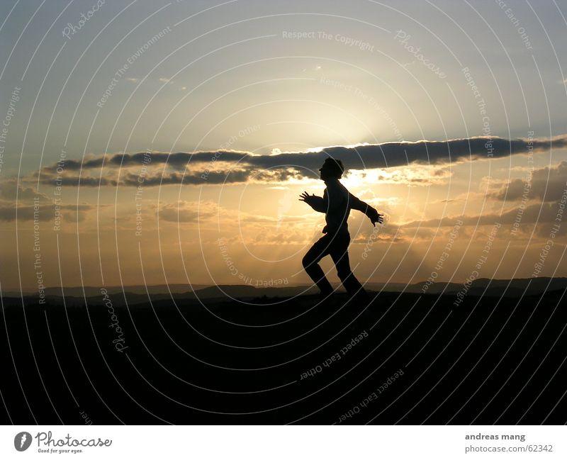 Reaching for the sun Mensch Mann Hand Himmel Sonne Freude Wolken springen Berge u. Gebirge Freiheit Landschaft Beleuchtung Horizont Abenddämmerung