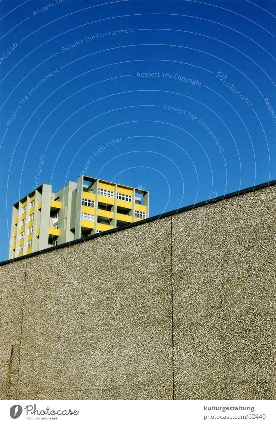 Berliner Plattenbau hinter einer Mauer Himmel blau Stadt Haus gelb Beton Hochhaus Balkon diagonal Osten