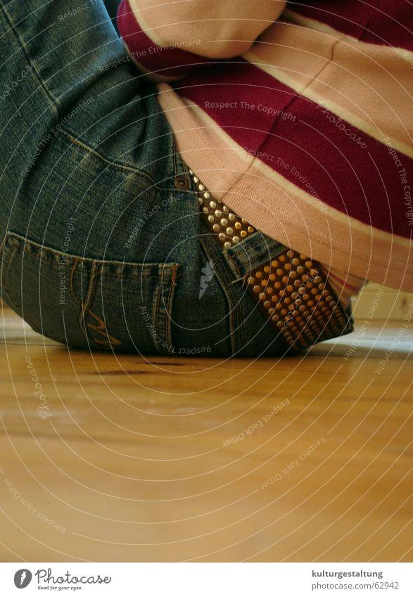 Sitzen auf dem Holzboden, hochkant Freizeit & Hobby aufhängen Jugendliche Mensch Pullover Gürtel Holzfußboden Detailaufnahme sitzen Coolness Jeanshose