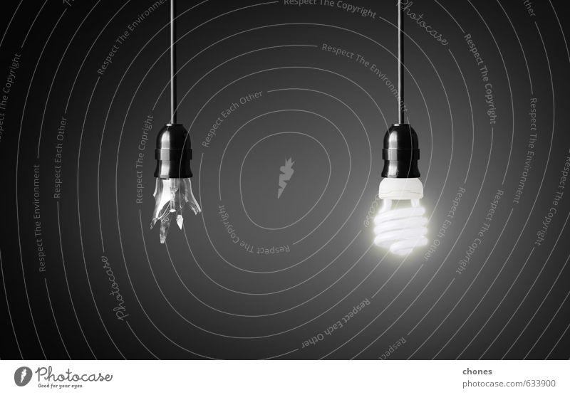 Eine kaputte und eine leuchtende Energiesparlampe. Design Lampe Technik & Technologie Energiewirtschaft Glas hell grün schwarz weiß Idee Kreativität Hintergrund